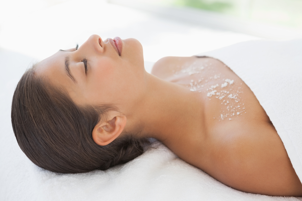 Beautiful brunette lying on massage table with salt scrub on chest at the health spa