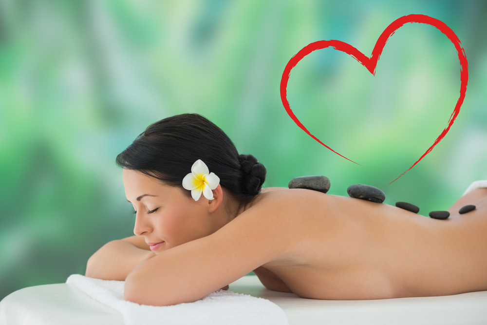 Beautiful brunette relaxing on massage table against heart