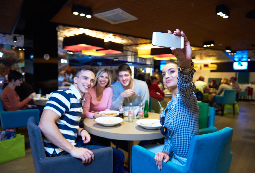 friends have lanch break in shopping mall, eating italian fast food